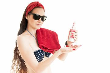 Summer stylish girl holding holding suntan lotion on whithe back
