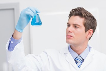 Scientist looking attentively at the beaker