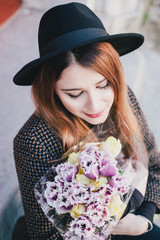 Pretty young woman wearing hat posing with flowers in her bag