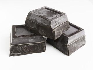 Tre blocchi di cioccolato fondente su sfondo bianco