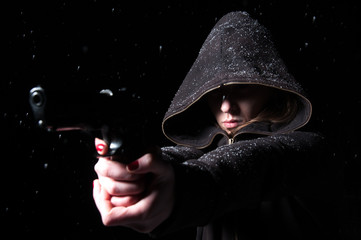 woman with a covered face holding a gun on a black background