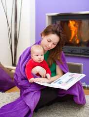 Mother is reading book with daughter