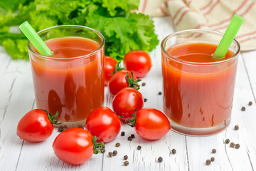 Refreshing glass of tomato juice with vegetables on background
