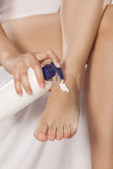 women applied the cream to her pretty feet on white