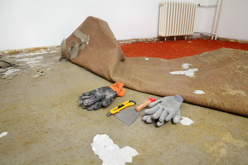 Home renovation, old carpet remove, tools and gloves