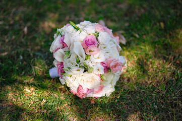 Beautiful bridal bouquet lying on the grass