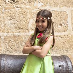 Niña con vestido verde y diadema de flores
