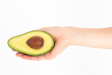 Woman presenting half of an avocado