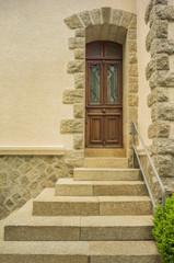 Eingang mit positiver Pyramidentreppe aus Granit und Holzhaustür