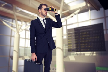 businessman holding a briefcase while using binoculars