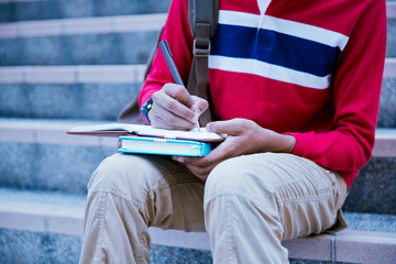 young college student reading book on stairs