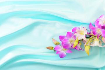 サテン生地のドレープと蘭の花