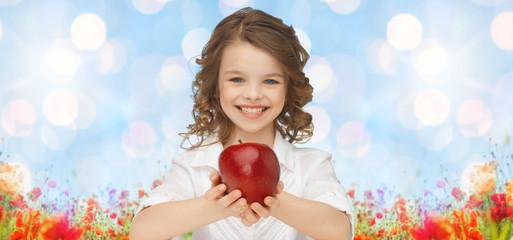 happy girl holding apple over garden background