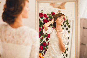 portrait of a model posing in the mirror. looking away