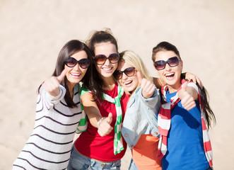 happy teenage girls showing thumbs up on beach