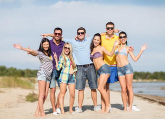 group of happy friends waving hands on beach