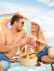 chappy ouple having picnic and sunbathing on beach