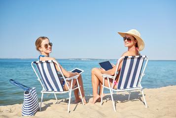 happy women with tablet pc sunbathing on beach