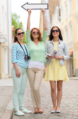 smiling teenage girls with white arrow outdoors