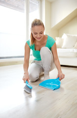 happy woman with brush and dustpan sweeping floor