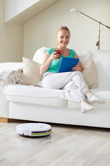 happy woman with tablet pc drinking tea at home