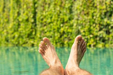 close up of male feet over resort swimming pool