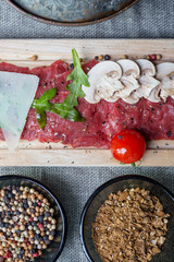 top view of traditional dish of beef carpaccio on wooden plate