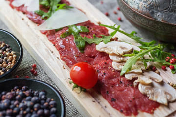 traditional dish of beef carpaccio on wooden plate with arugula