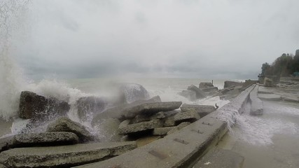 High waves crashing against the rocks. Black sea. The gray sky