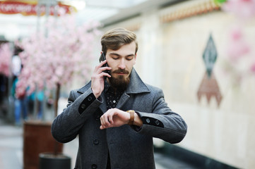 stylish man with a beard and mustache, talking on a cell phone a