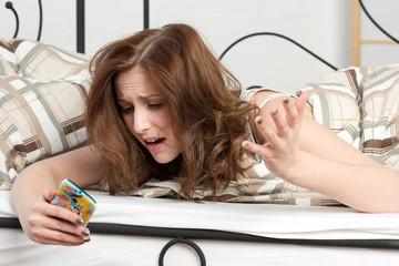 Frau im Bett mit Handy ist wütend