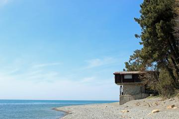 Домик на каменистом морском берегу. Есть место для текста