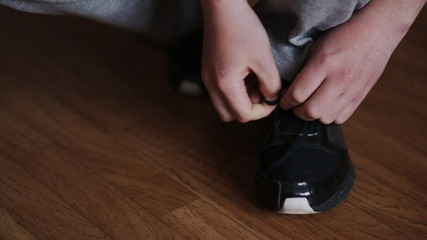 guy tying the laces on black sneakers