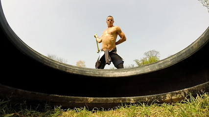 Close up of a man hitting tire with a hammer in one hand