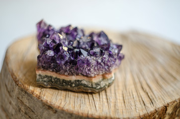 Raw amethyst rock with reflection on natural wood