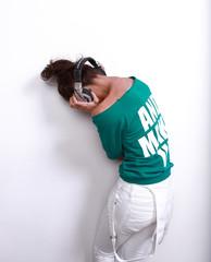 girl in green jacket poses  in  DJ's earphones