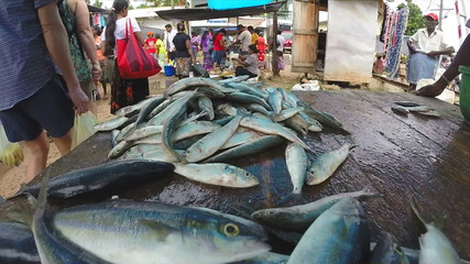 HIKKADUWA, SRI LANKA - MARCH 2014: Fresh fish on the table at market in Sri Lanka, customers passing by.