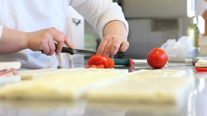 hands prepare sandwich with tomato mozzarella