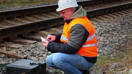 Worker with tablet PC phone near railway