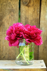 Red peonies in glass jar on wood background