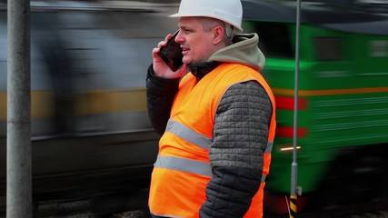 Railway employee talking on cell phone near the passing train