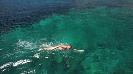 Man swimming in mediterranean close to sailing boat