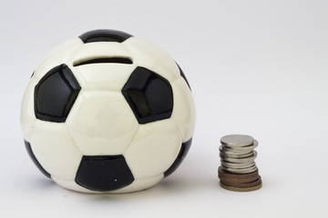 Football ball moneybox and money on a white background