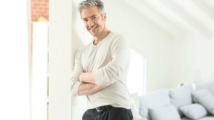 Mature handsome man standing inside home