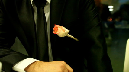 Sitting bridegroom wearing rose on his tux waiting on bride