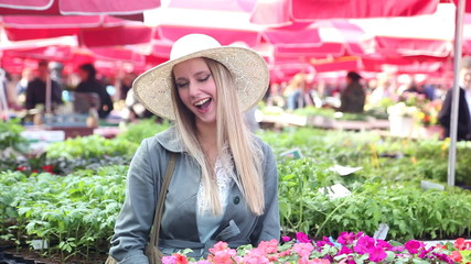 Pretty blonde woman in the flower market, winking