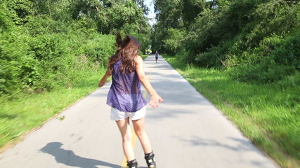 Young attractive woman rollerblading in park on a beautiful sunny day.