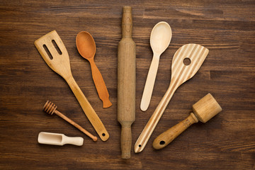 Wooden kitchen tools on vintage wooden background.