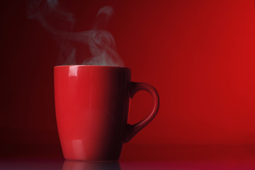 Red cup with steam over red background