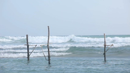 GALLE, SRI LANKA - MARCH 2014: View of local fishing poles in the ocean in Galle. Stilt fishing is a tradition that only about 500 fishing families in the district of Galle practice.
